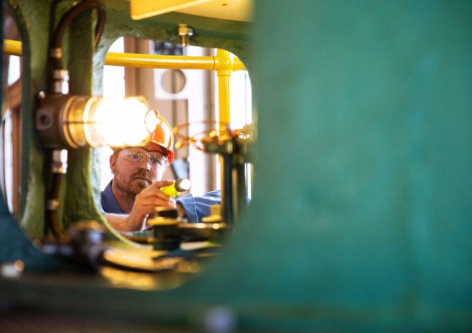 A hydroelectric worker examines machinery with a pen light.