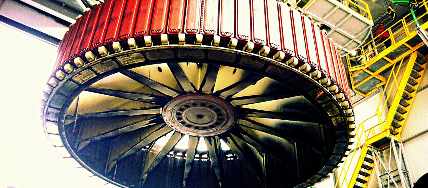 A rotor from a generating unit suspended in the air for maintenance.