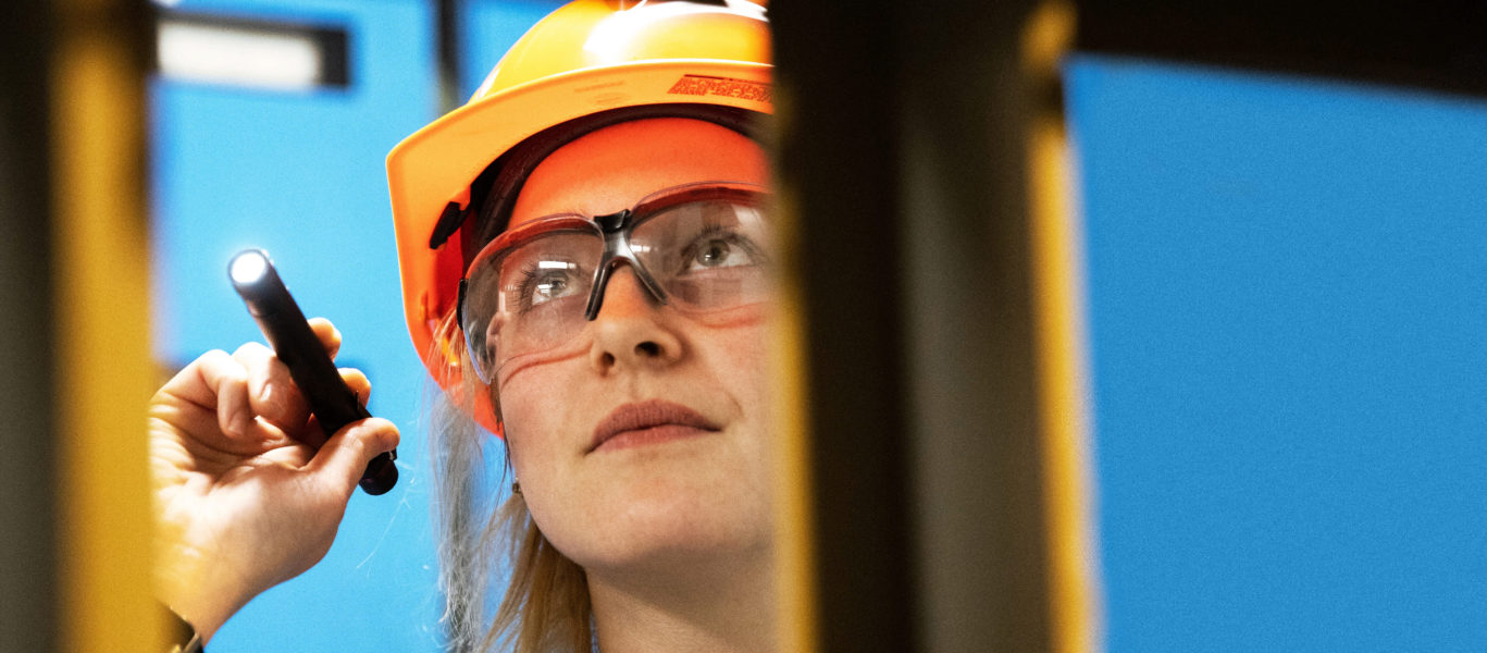 A female worker in safety glasses and a hard hat examines with a pen light.